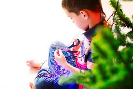 electric shock: un segundo antes de la descarga eléctrica. niño curioso con un par de tijeras en la mano tratando de desmantelar las luces de Navidad para ver lo que hay dentro. sobre la opinión del hombro Foto de archivo