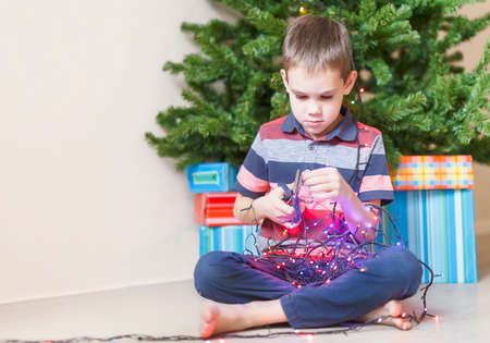 dismantle: dangerous children antics. curious boy with a pair of scissors in his hand trying dismantle the Christmas lights to see what is inside