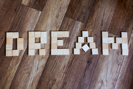 reverie: dream made of wood. the word dream inlaid wooden toy blocks on wooden background