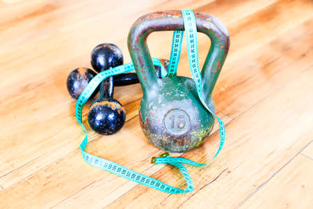 gaining: strength training. weight and dumbbells belted measuring tape symbolize a way of gaining a beautiful and healthy body