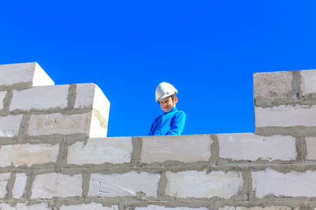boy on a building site. boy playing in a helmet on a construction site
