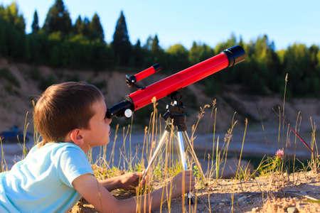 astronomie: Junge in der Dämmerung Blick durch ein Teleskop. Junge in der Morgendämmerung Sonne schaut durch ein Teleskop, während man auf einem Hügel