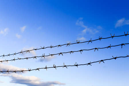 pokey: three rows of barbed wire.three rows of barbed wire diagonally against the blue sky