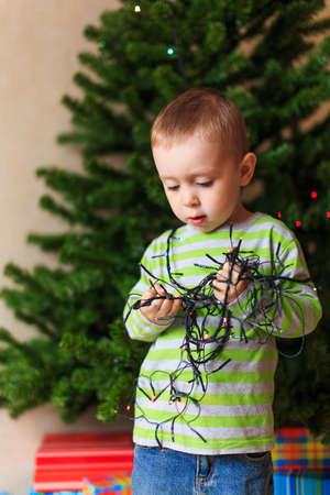 electroshock: risk of fire at Christmas. little boy plucked with Christmas tree of Christmas lights and keeps them in the hands of Stock Photo