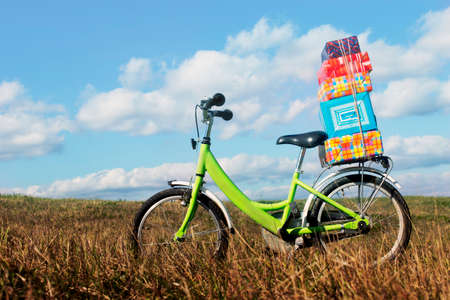 foretaste: Bike with gifts. bike stands in the middle of the field with a pile of gift boxes, the concept of the upcoming holiday