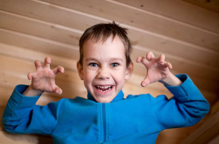 scaring: boy scares and makes faces. cheerful boy poses scary faces and frightening