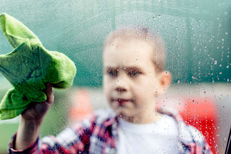 wash cloth: child washes car window. inside view: A boy cloth washes the dirty glass of the car Stock Photo