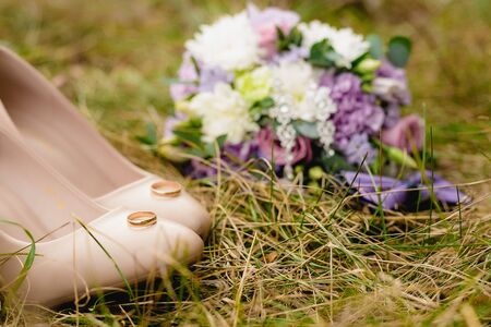 Beige wedding shoes, pair of engagement rings, bow-tie and bouquet on the grass.