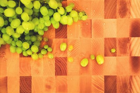 Fresh green grape on the wooden cutting board, top view