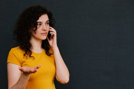 Portrait of funny emotional curly girl,talking to phone, on grey background. Surprise. Upset. Joy. Fright. Happy. Sadness Copy space