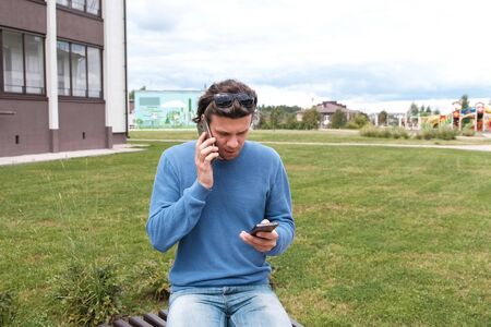 Man with two mobile phones on the bench near the home Stock Photo
