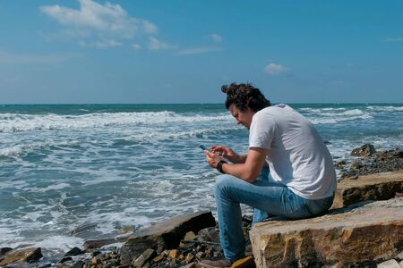 Young man types a message on mobile phone sitting on the big stone on sea beach. Big waves beating against the shore