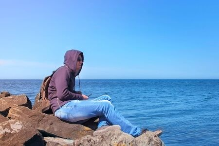 Young man tourist admires seascape sits on huge stone boulder on sea shore. Guy traveller in sunglasses, jeans and sweatshirt on sea spring vacation. Travel journey trip with backpack at sunny day.