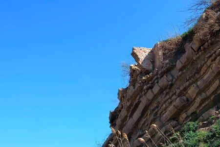 Ruins of brick house on top of broken rock mountain after earthquake tsunami nature disaster on blue sky background. Ancient building on rock in mountains.
