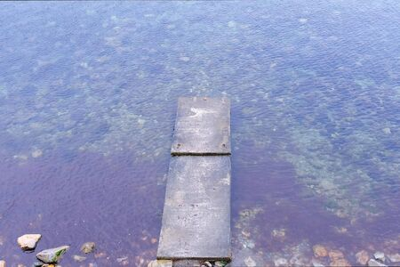 Old concrete destroyed pier at sea. Transparent water with seaweeds and stone seabed, top view. Ripples from wind on water surface. Outdoors nature sescape.