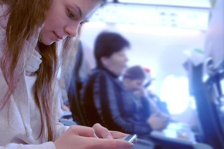 Woman playing a game on a mobile phone while flying a plane. Passengers on Board the aircraft