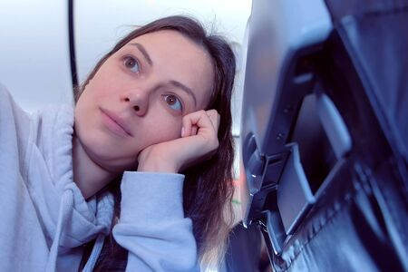 Woman on Board the plane. Fear of flying and looking out the window