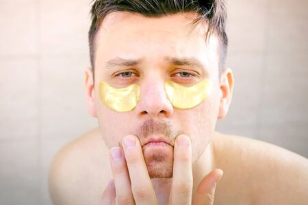 Funny man with golden patches under eyes touching moustache looking at camera and smiling, front view. He is putting himself in order making hygienic and beauty procedures. Archivio Fotografico - 133383795