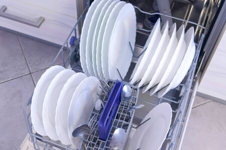 Clean white dishes tableware and cutlery in basket of built-in dishwasher in kitchen, top view. Open dishwasher mashine with dishes, closeup view. 写真素材