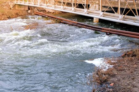 Rapid flow of river under bridge in city, rusty pipes laid across the river. Fast flow of water with foam between two banks with ground.