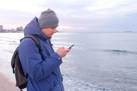 Man is typing message on smartphone in coastal town at sea in winter. Man traveller freelancer blogger is writing post on phone. Tourist travel journey trip with backpack.