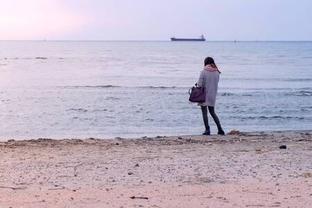 Young woman admires sea view on sunset at sea beach in winter, back view. Girl in grey coat standing at seashore and looking at distnce. Traveler, travel, journey, tourism, trip on vacation.