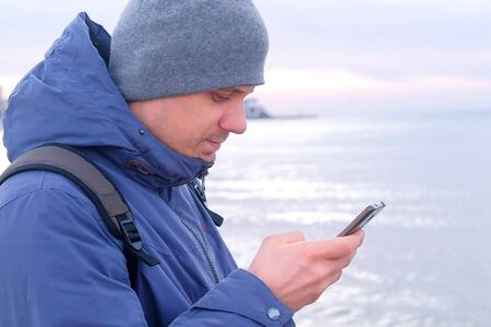 Portrait of man is typing message on smartphone in coastal town at sea in winter, side view. Man traveller freelancer blogger is writing post on phone. Tourist travel journey trip with backpack.