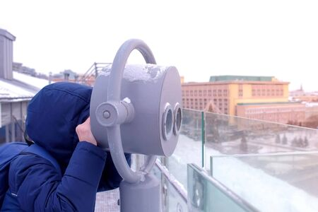 Unrecognizable child boy looking through binoculars on observation deck on roof of building in city in winter. Portrait of teen traveler in warm jacket and hat. Travel, journey and tourism concept. Standard-Bild