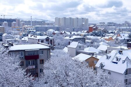 View of small town with mountains with houses covered snow in winter. Southern city in winter overcast weather with falling snow. 版權商用圖片