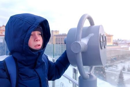 Boy looks through binoculars on the observation deck on the roof of the building in the city in winter. Portrait of child boy traveler in warm jacket and hat. Travel, journey and tourism concept.