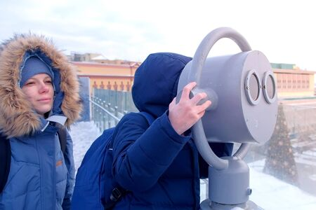 Mom and son look through binoculars on the observation deck on the roof of the building in the city in winter. Family travelers in warm jackets and hats. Travel, journey and tourism concept.