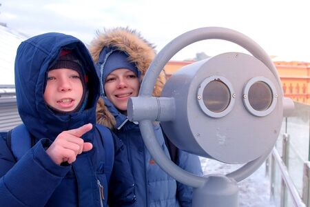 Mom and son look through binoculars on the observation deck on the roof of the building in the city in winter. Family travelers in warm jackets and hats. Travel, journey and tourism concept. Standard-Bild