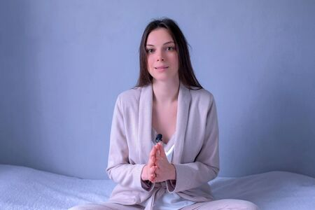 Portrait of woman blogger talking on video and looking at camera at home sitting on bed. Vlogger tells information to her followers looking at camera on grey background. Modern freelance job, work.