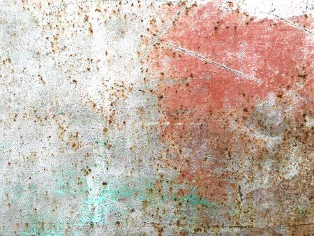 Old iron wall with scratches and rust covered with blue and green and pink paint. Abstract colored old background.