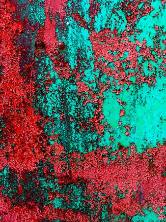 Iron green wall with old red paint in the crack. Abstract grunge background.