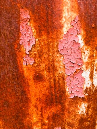 Old iron wall with scratches and rust covered with pink paint. Abstract background.