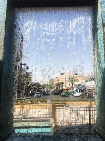 View of the city street through the falling water of the fountain. Jordan, Aqaba.