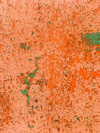 Iron wall with old orange and green paint in the crack. Grunge background. 写真素材