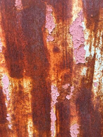 Old iron wall with scratches and rust covered with pink paint. Abstract grunge background.
