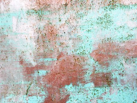 Old iron wall with scratches and rust covered with blue and green and pink paint. Grunge old colored background. 写真素材
