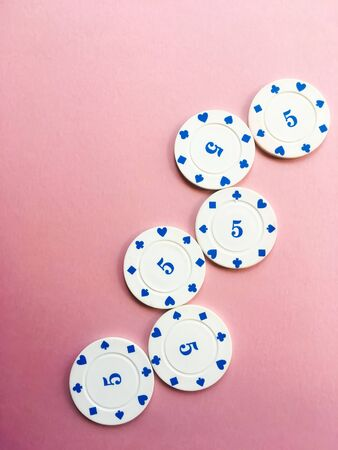 Chips for poker on pink background. Copy space.
