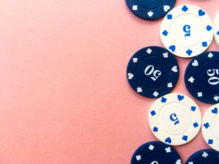 Chips for poker on pink background. Five and fifty chips. Copy space.