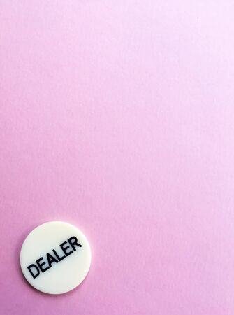 Chips for poker on pink background. Dealer chip. Poker play. Copy space. Banco de Imagens