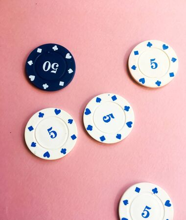 Blue and white casino chips on pink background. Five and fifty chips.