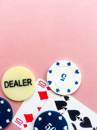 Chips and cards for poker on pink background. Dealer chip. Gambling. Place for text. Stok Fotoğraf