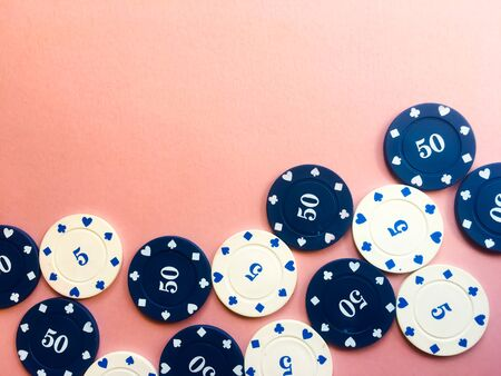 Chips for poker on pink background. Five and fifty chips. Poker play. Copy space. Banco de Imagens