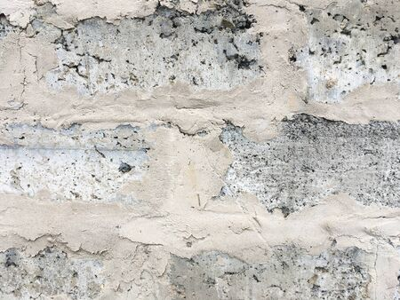 Old gray brick wall covered with concrete. Abstract background. Texture for design.