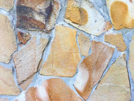 Wall of broken shapeless brick. Orange grunge background. Abstract background.