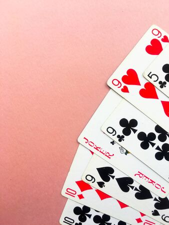 Cards for playing poker lie in the coner of a pink background. Place for text. Gambling.
