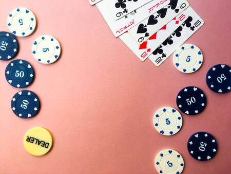 Poker chips and cards on a pink background. The game of poker. Chip dealer. Gambling. Place for text.